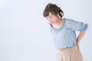 腰をおさえている女性の画像